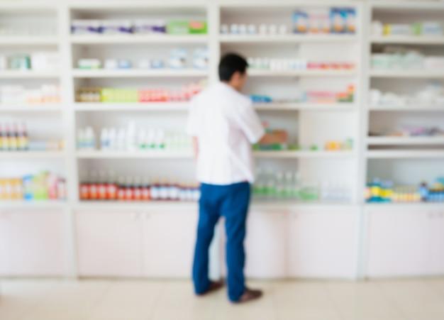 Zamazany obraz farmaceuty biorącego lekarstwa z półki w aptece
