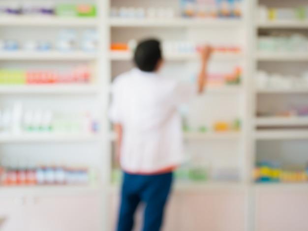Zamazany obraz farmaceuty pracującego w aptece