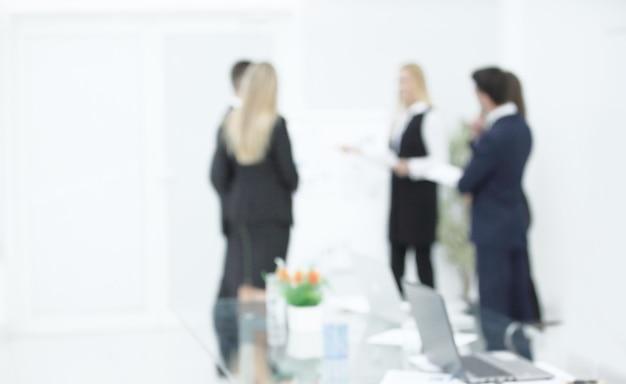 Zamazany obraz grupy ludzi biznesu na tle biura.