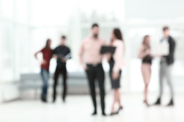Zamazany obraz grupy ludzi biznesu rozmawiających w holu urzędu. zaplecze biznesowe