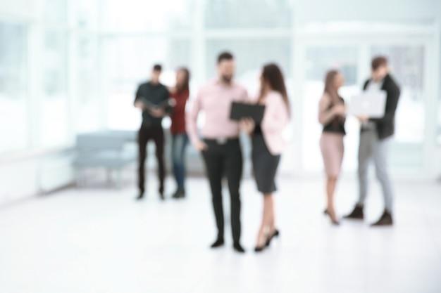 Zamazany obraz grupy ludzi biznesu rozmawiających w holu urzędu. zaplecze biznesowe.