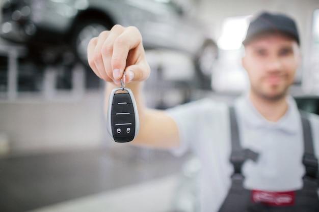 Zamazany obraz klucza, który pracownik trzyma w ręku. patrzy na to i lekko się uśmiecha. młody człowiek stać w garażu. za nim na platformie jest samochód.