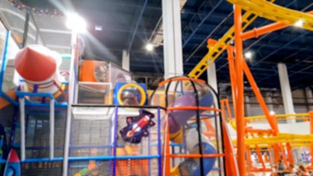 Zamazany obraz kolorowego placu zabaw dla dzieci i kolejki górskiej w parku rozrywki w centrum handlowym