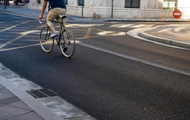 Zamazany obraz mężczyzny jadącego na rowerze w miejskim mieście dojeżdżającym z prędkością i modnym transportem hipster
