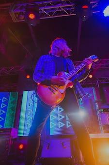 Zamazany obraz muzyk rockowy na abstrakcyjnym koncercie ze światłami scenicznymi. koncert abstrakcyjnego zespołu rockowego