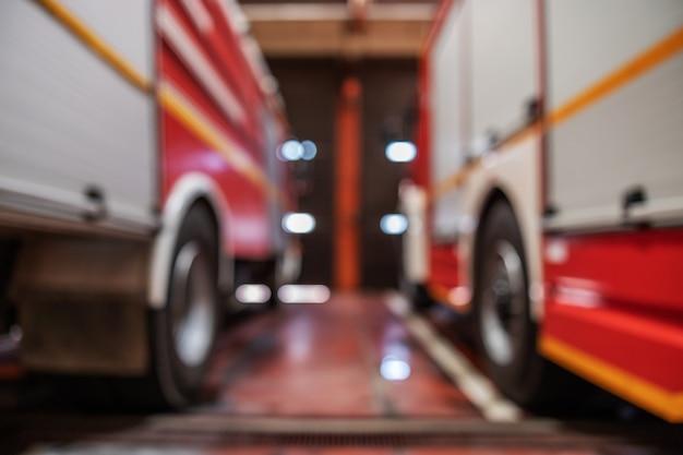 Zamazany obraz wozów strażackich zaparkowanych w straży pożarnej.