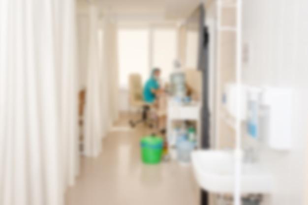 Zamazany oddział szpitalny z łóżkami i sprzętem medycznym