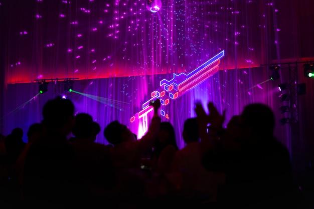 Zamazany pojęcie przy koncertowym przyjęciem z widownią i kolorowym dowodzonym oświetleniem.