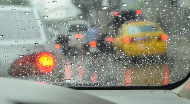 Zamazany samochód widziany przez mokrą przednią szybę w deszczowy dzień