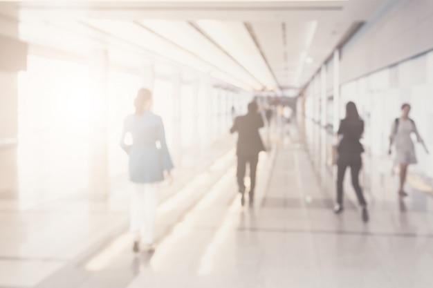 Zamazany tło biznesmeni chodzi w korytarzu centrum biznesu