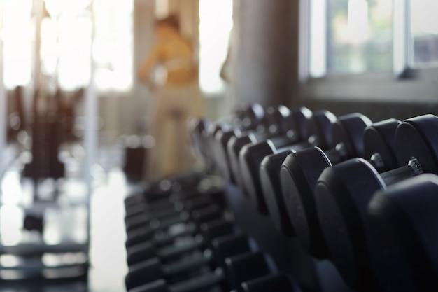 Zamazany tło rzędy czarni dumbbells na stojaku w gym