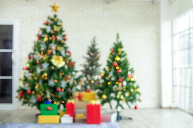 Zamazany widok choinki z czerwonymi prezentami. dekoracja w okresie bożego narodzenia i nowego roku.