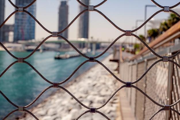 Zamazany widok na miasto przez metalową siatkę