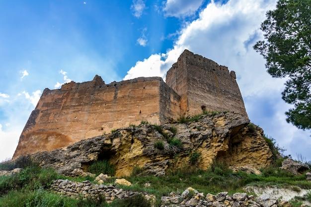 Zamek barxell w dzień z błękitnym niebem z białymi chmurami i promieniami słońca wschodzącymi za nim.
