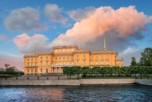 Zamek michajłowski w sankt petersburgu koło fontanki w promieniach zachodzącego słońca i wielkiej różowej chmurce