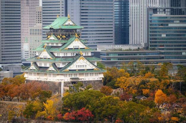 Zamek osaka z ogrodem japońskim i wieżowcem biurowca miejskiego jesienią w osace