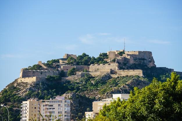 Zamek santa barbara alicante na szczycie wzgórza nad miastem. w słoneczny dzień. kamienna forteca. comunidad valenciana.