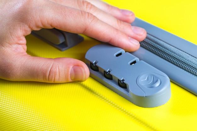 Zamek szyfrowy na żółtej walizce do podróży.