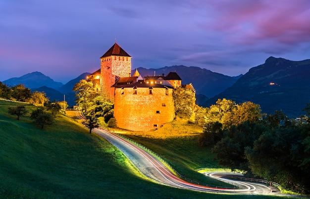 Zamek vaduz z krętą drogą w liechtensteinie nocą