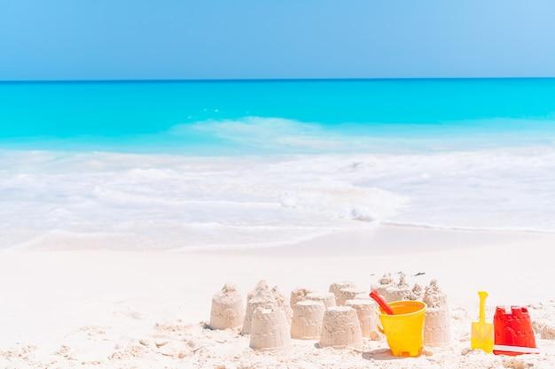 Zamek z piasku na białej tropikalnej plaży z plastikowymi zabawkami dla dzieci