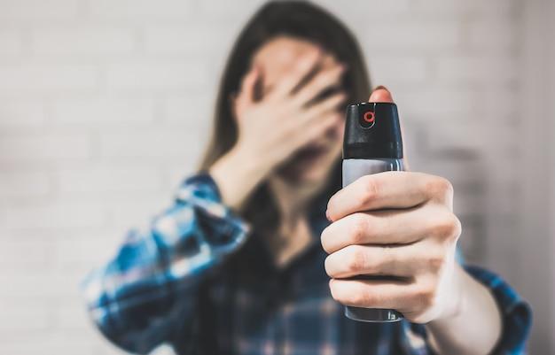 Zamężna kobieta trzyma kanister z gazem pieprzowym dla ochrony osobistej. dziewczyna zakrywa twarz rękami. białe tło z tyłu. zdjęcie samoobrony. skopiuj miejsce.