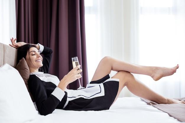 Zamiast pracy. pozytywna pokojówka hotelowa odpoczywa na łóżku, nie chcąc pracować