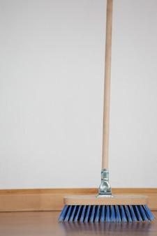 Zamiatająca miotła z drewnianym uchwytem na podłodze