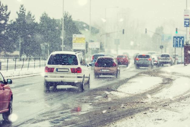 Zamieć na drodze o słabej widoczności, samochody ze światłami na skrzyżowaniu.