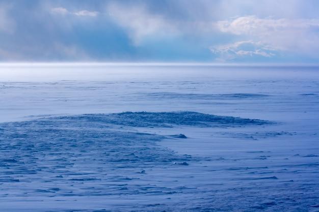 Zamieć nad jeziorem bajkał zimą. silny wiatr i dużo śniegu. niebieski odcień śniegu. chmury na niebie. poziomy.