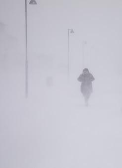 Zamieć w longyearbyen, kobieta idąca w śniegu. abstrakcjonistyczny rozmyty zimy pogody tło