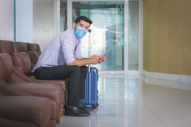 Zamknąć biznesmen noszenie maski na twarz siedzi samotnie w holu hotelu.