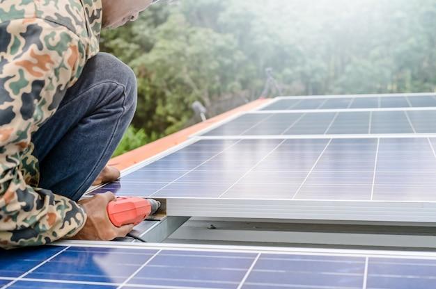 Zamknąć człowieka instalującego panele słoneczne na domu na dachu w celu zapewnienia bezpiecznej energii fotowoltaicznej alternatywnej energii. moc z natury energia słoneczna generator ogniw słonecznych oszczędza ziemię.