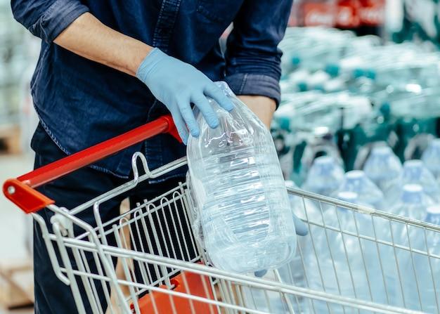 Zamknąć klienta w masce ochronnej wybierając wodę butelkowaną