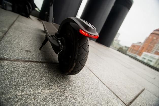 Zamknąć koło hulajnogi. wygodny sposób podróżowania. płyty betonowe po deszczu. duże miasto w tle. skuter elektryczny. ekologiczna koncepcja transportu.