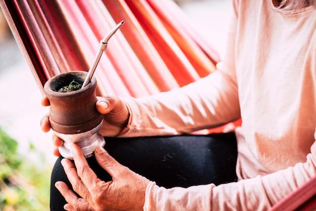 Zamknąć kolorowy obraz ze starymi starszymi rękami kaukaski kobieta pije naturalną herbatę z drewnianego kubka