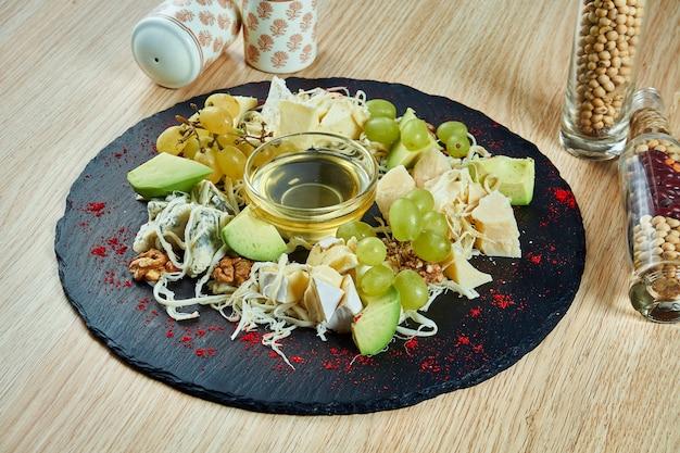 Zamknąć na talerzu serowym (cheeseboard) podawanym z orzechami, winogronami, miodem. z bliska na różnych rodzajach sera na drewnianym stole