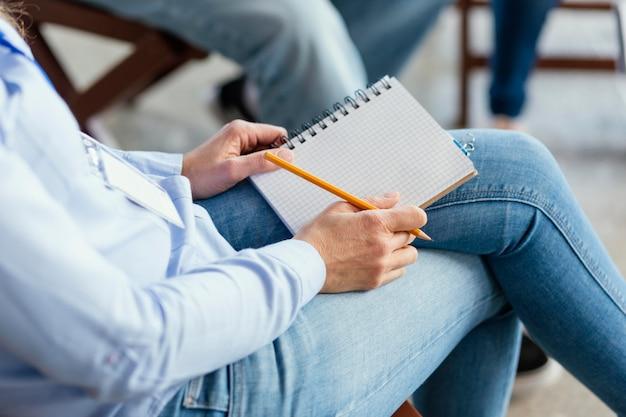 Zamknąć ręce notatnikiem i ołówkiem