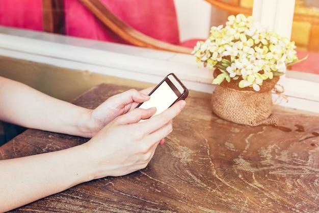 Zamknąć rękę kobieta przy użyciu telefonu w kawiarni z rocznika stonowanych.