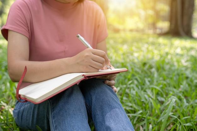 Zamknąć siedzi pisanie na notebooku w parku