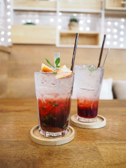 Zamknąć szklankę soku truskawkowego z sodą na drewniany spodek nad drewnianym stołem w restauracji obiadowej