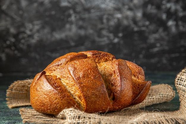 Zamknąć widok bochenka czarnego chleba dietetycznego na brązowy ręcznik na powierzchni ciemnych kolorów z wolnej przestrzeni
