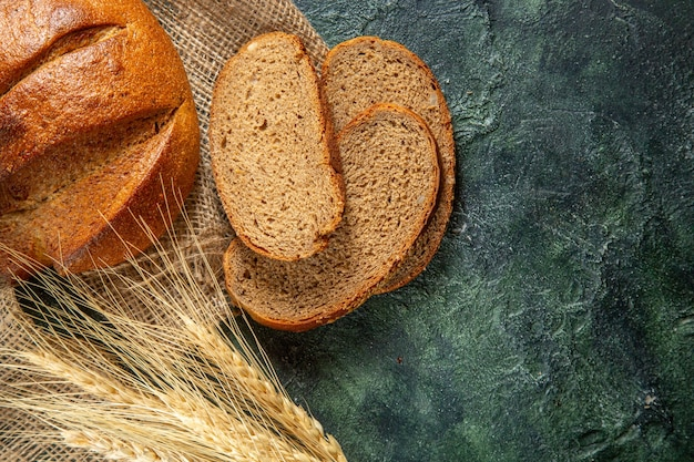Zamknąć widok całego i pokroić dietetyczny czarny chleb i kolce na brązowy ręcznik na powierzchni ciemnych kolorów