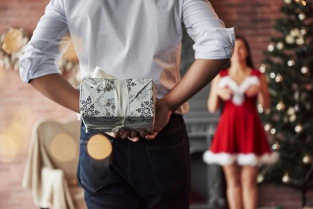 Zamknąć widok. człowiek stoi i trzyma pudełko za. kobieta w czerwonej sukience otrzyma teraz prezent świąteczny od chłopaka.