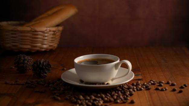 Zamknąć widok filiżanki gorącej kawy z koszem bagietki i ziaren kawy na stole śniadanie