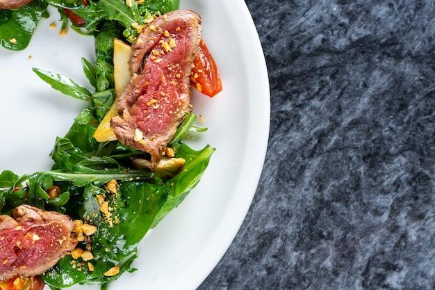 Zamknąć widok na sałatkę tataki w stylu kuchni japońskiej ze szpinakiem beaf, rukolą. wołowina tataki. jedzenie w restauracji na lunch. płaskie jedzenie leżało na marmurowym stole.