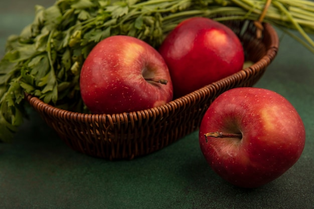 Zamknąć widok świeżych czerwonych jabłek i pietruszki w wiadrze na zielonej powierzchni