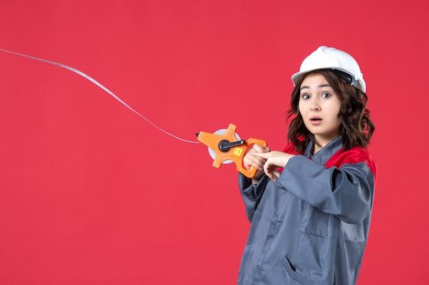 Zamknąć widok zmartwionych kobiet architekta w mundurze z kaskiem otwierającym taśmę pomiarową na odosobnionej czerwonej ścianie