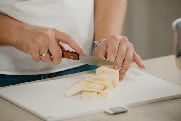 Zamknąć zdjęcie z rąk młodej kobiety cięcia świeżego masła farmy na pokładzie rozbioru z ostrym nożem