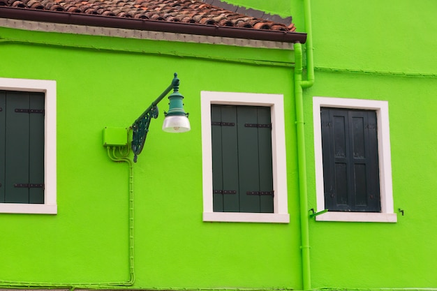 Zamknięci okno z drewnianymi żaluzjami i rocznik lampą na zielonej kolorowej ścianie w burano blisko wenecja, włochy