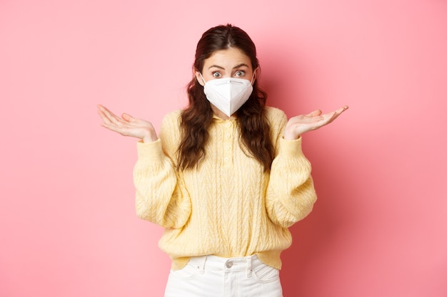 Zamknięcie covid i koncepcja pandemii nieświadoma młoda kobieta w respiratorze medycznym nic nie wie, wzrusza ramionami ze zdezorientowaną twarzą, nie ma pojęcia, stojąc nad różową ścianą